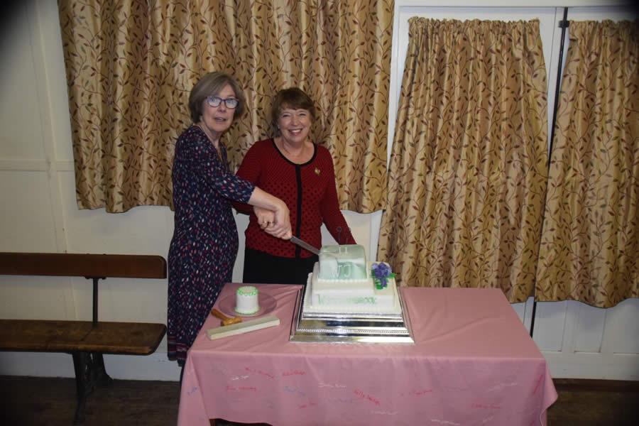 W.I. 90th Anniversary cutting cake